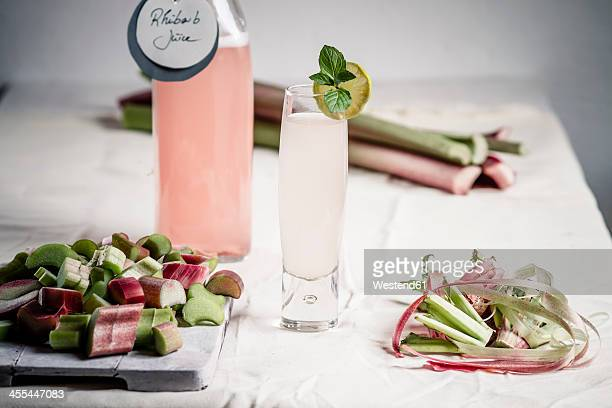 pieces of rhubarb on cutting board with glass and bottle of rhubarb juice - rhubarb stock photos and pictures