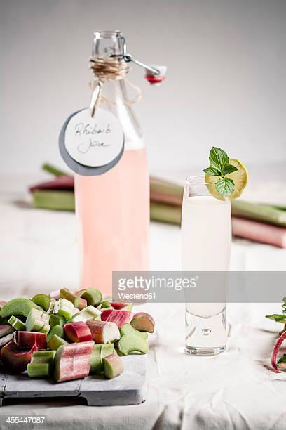 Pieces of rhubarb on cutting board with glass and bottle of rhubarb juice