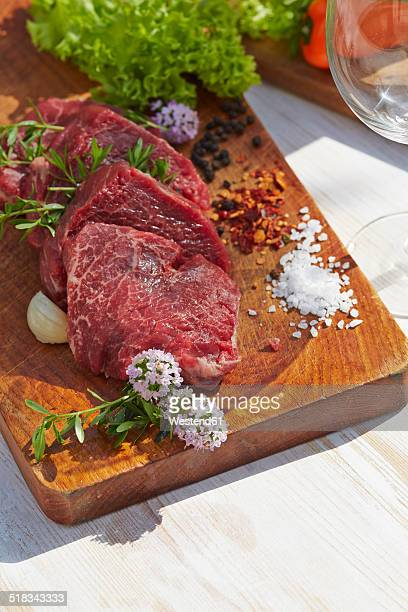 Pieces of sirloin and spices on chopping board