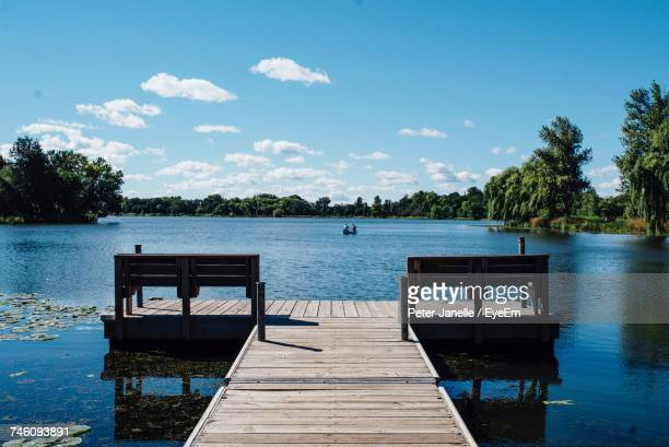 Pier Amidst Lake Against Blue Sky On Sunny Day