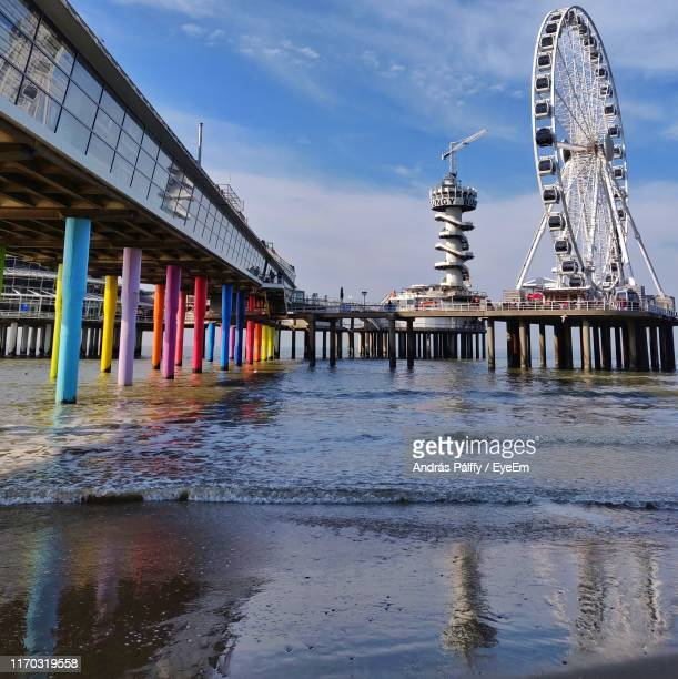pier and ferris wheel over sea against sky - the hague stock pictures, royalty-free photos & images