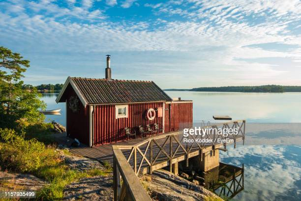 pier and hut by calm lake against cloudy sky - sweden stock pictures, royalty-free photos & images