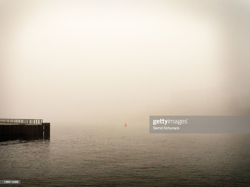 Pier and red buoy in fog : Stock-Foto