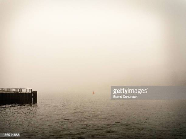 pier and red buoy in fog - bernd schunack stock-fotos und bilder