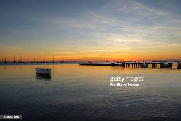 pier and small boat in sunrise at mar menor - la manga cityscape in the background - finn bjurvoll stock photos and pictures