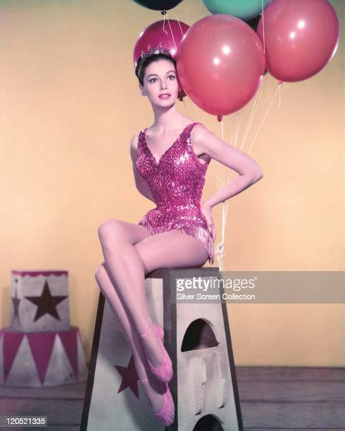 Pier Angeli Italian actress wearing a fringed red sequinned leotard while sitting on a circus podium with balloons in the background in a publicity...