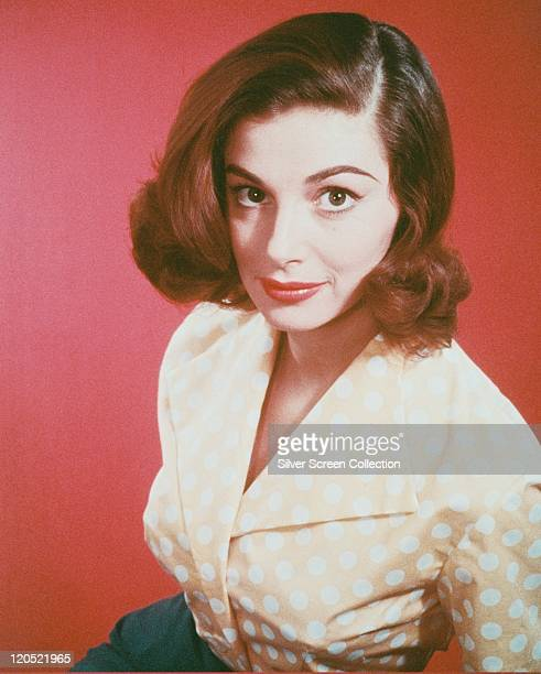 Pier Angeli Italian actress wearing a peach blouse with white polka dots in a studio portrait against a red background circa 1960