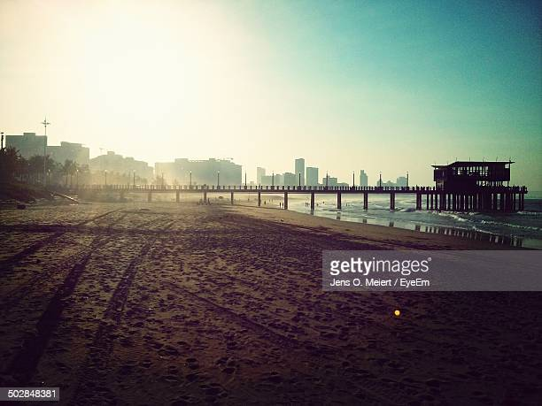 pier at beach against clear blue sky - durban beach stock photos and pictures