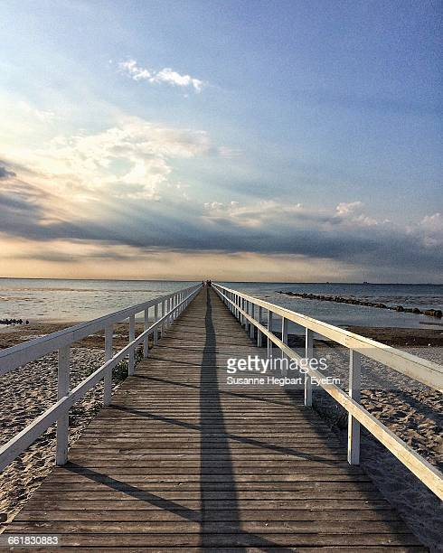 Pier At Beach Against Cloudy Sky During Sunny Day