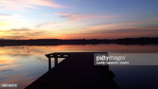 pier at calm lake against sky during sunset - sabine hauswirth stock pictures, royalty-free photos & images