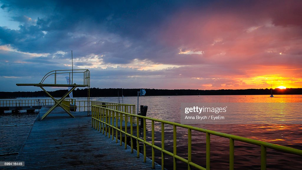Pier By Lake Against Cloudy Sky During Sunset At Masuria : Stock Photo