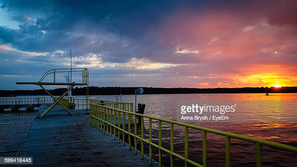 Pier By Lake Against Cloudy Sky During Sunset At Masuria