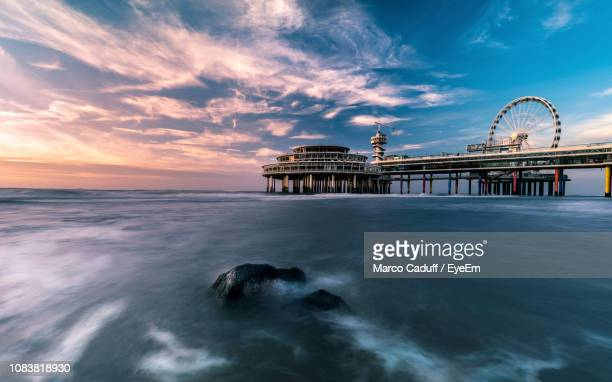 pier by sea against cloudy sky during sunset - the hague stock pictures, royalty-free photos & images