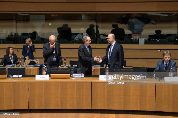 Pier Carlo Padoan Italy's finance minister center shakes hands with Pierre Moscovici economic commissioner for the European Union ahead of an Ecofin...