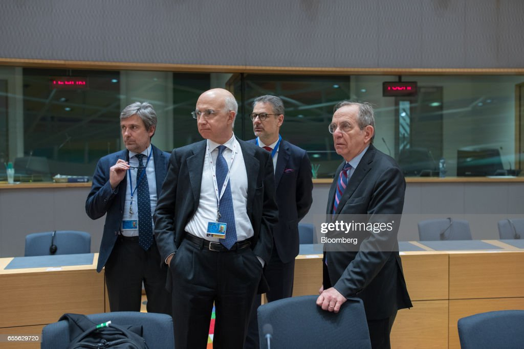 Pier Carlo Padoan, Italy's finance minister, right, stands with members of his delegation ahead of a Eurogroup meeting of finance ministers in Brussels, Belgium, on Monday, March 20, 2017. Wolfgang Schaeuble, Germany's finance minister, said to reporters ahead of the meeting of euro-area finance ministers Well get a report on Greece, but the mission isnt completed,. Photographer: Jasper Juinen/Bloomberg via Getty Images