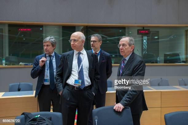 Pier Carlo Padoan Italy's finance minister right stands with members of his delegation ahead of a Eurogroup meeting of finance ministers in Brussels...