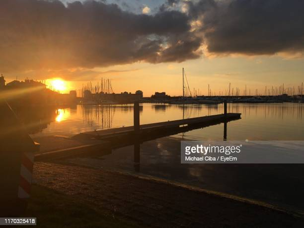 pier in city against cloudy sky during sunset - ciba stock pictures, royalty-free photos & images
