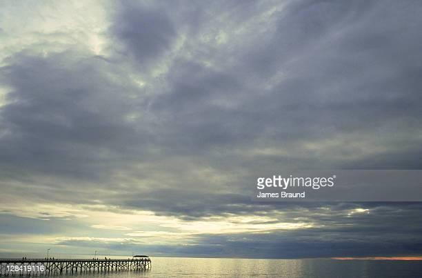 pier in late afternoon under stormy sky - calm before the storm stock pictures, royalty-free photos & images