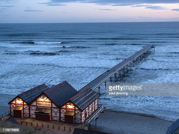 pier in sea at dawn, saltburn - saltburn stock photos and pictures