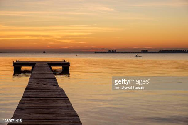 pier in sunrise at mar menor - la manga cityscape in the background - finn bjurvoll stock photos and pictures