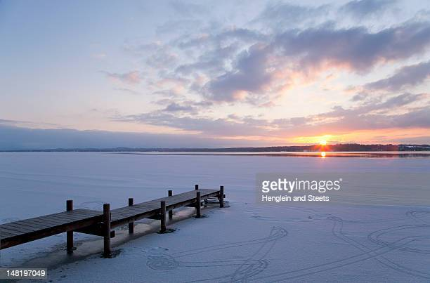 pier jutting out into frozen lake - jour photos et images de collection