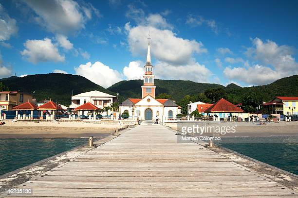 pier leading to church in caribbean - martinique stock photos and pictures