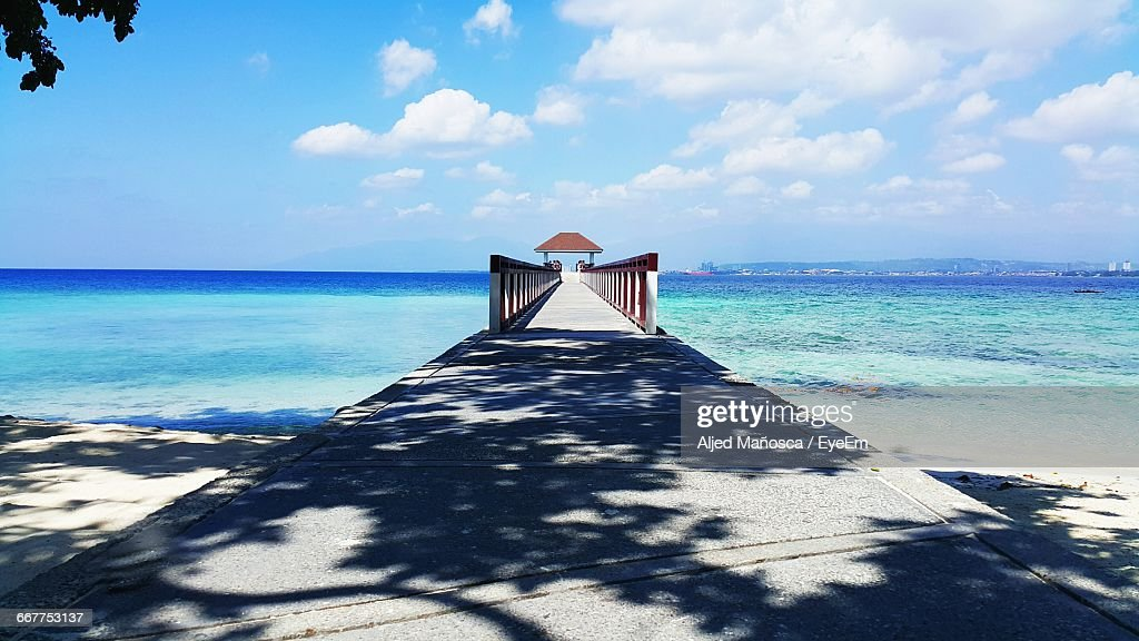 Pier Leading Towards Gazebo At Beach Against Cloudy Sky During Sunny Day : Stock Photo