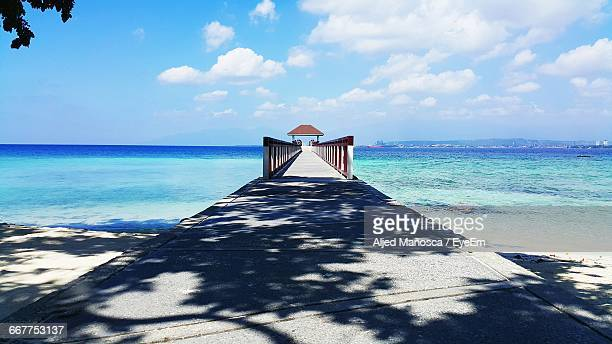pier leading towards gazebo at beach against cloudy sky during sunny day - davao city stock photos and pictures