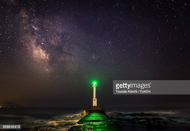 Pier Leading Towards Illuminated Lighthouse In Front Of Sea At Night