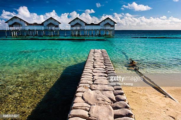 Pier make of sandbag facing row of deluxe family water villas at Centara Grand Island Resort & Spa Maldives.