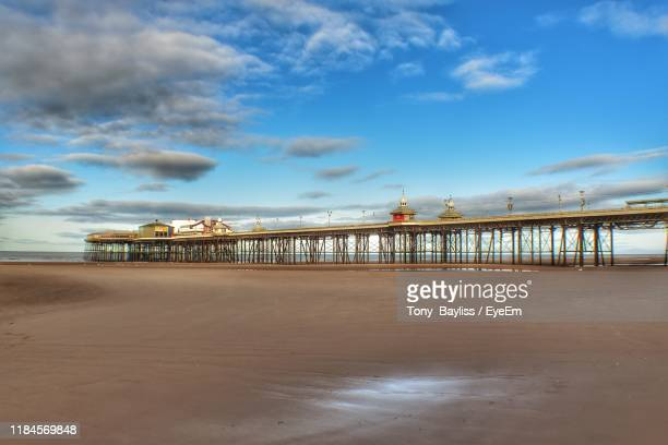 pier on beach against cloudy sky - blackpool beach stock pictures, royalty-free photos & images