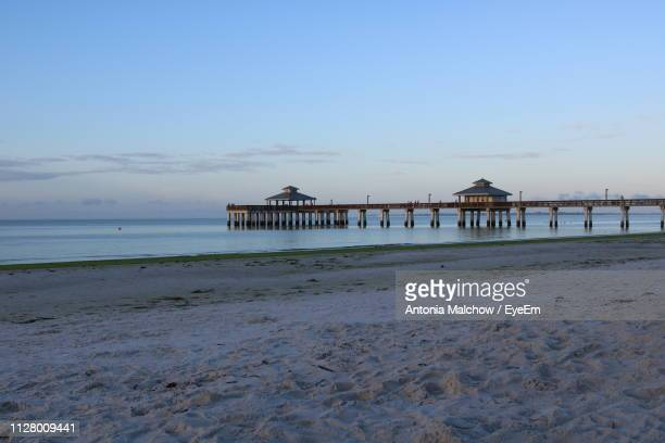 pier on beach against sky during sunset - fort myers beach stock pictures, royalty-free photos & images