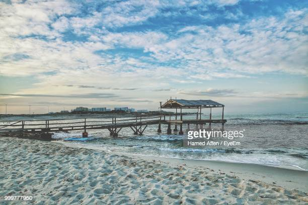pier on beach against sky during sunset - tunisia stock pictures, royalty-free photos & images