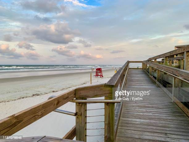pier on beach against sky - julie culy stock pictures, royalty-free photos & images