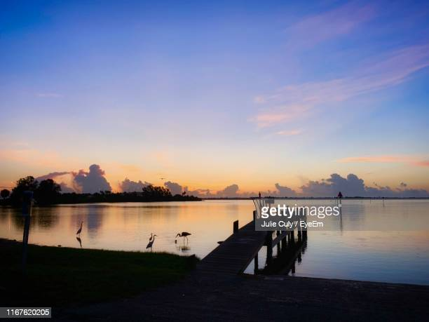 pier on lake against sky during sunset - julie culy stock pictures, royalty-free photos & images
