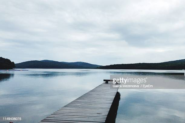 pier on lake against sky - jetty stock pictures, royalty-free photos & images
