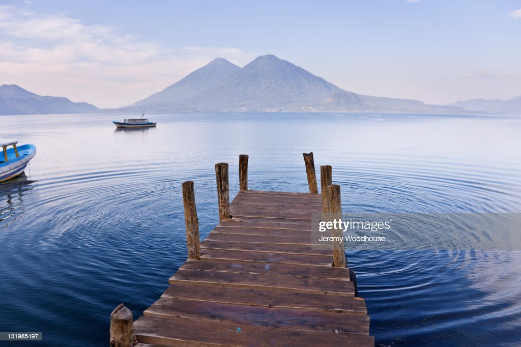 Pier on lake with mountain in distance : Stock Photo