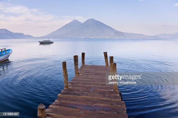 Pier on lake with mountain in distance