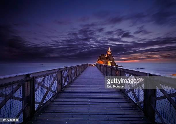 Pier on ocean at sunset, Le Rocher de la Vierge