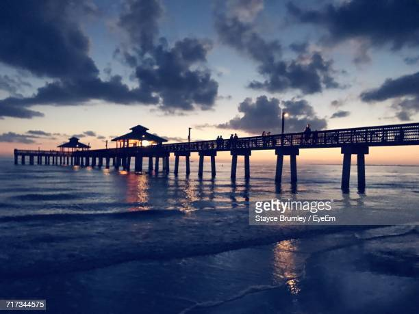 pier on sea against cloudy sky - fort myers beach stock photos and pictures