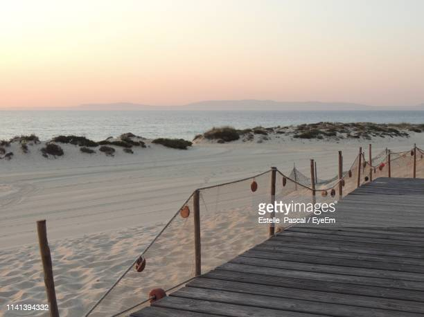 pier on sea against sky during sunset - comporta portugal stock photos and pictures