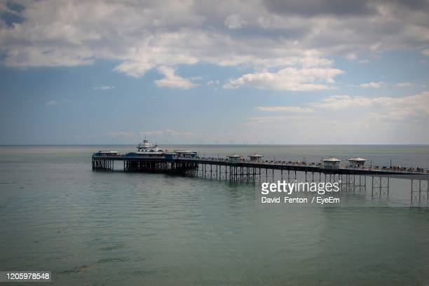pier on sea against sky - llandudno wales stock pictures, royalty-free photos & images