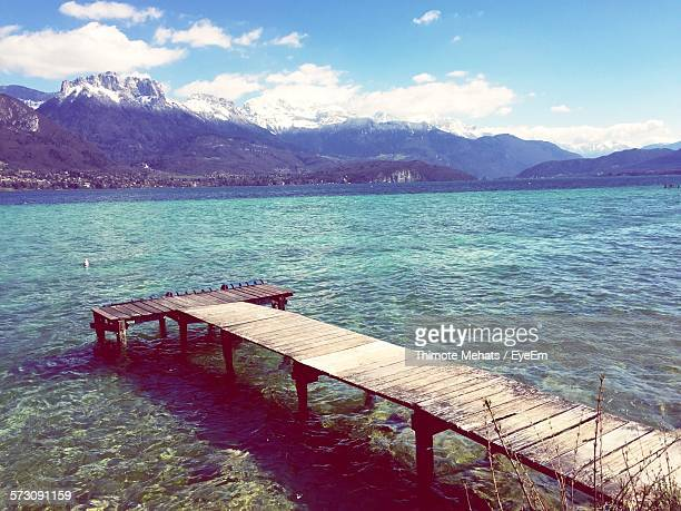 Pier Over Annecy Lake By Mountains Against Sky