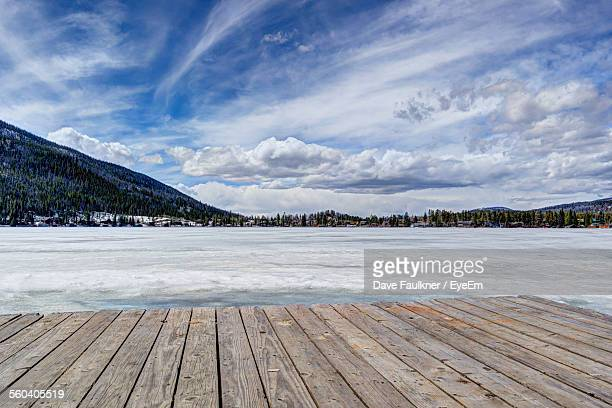 Pier Over Frozen Lake Against Sky