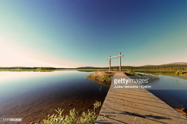 pier over lake against clear blue sky - heinovirta stock photos and pictures