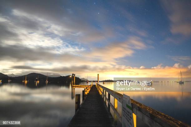 pier over lake against sky at sunset - whangarei heads stock-fotos und bilder