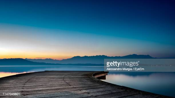 pier over lake against sky during sunset - jetty stock pictures, royalty-free photos & images
