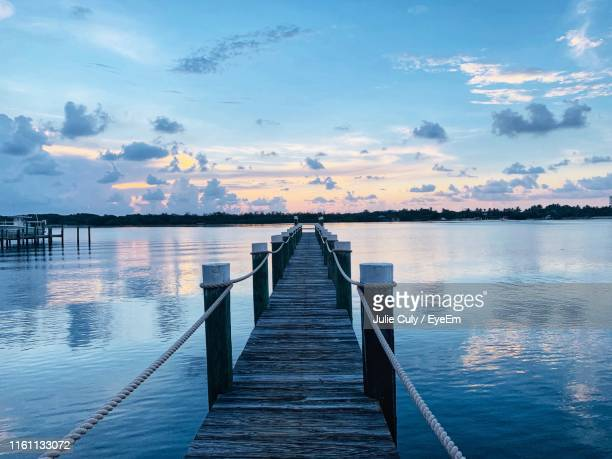 pier over lake against sky during sunset - julie culy stock pictures, royalty-free photos & images