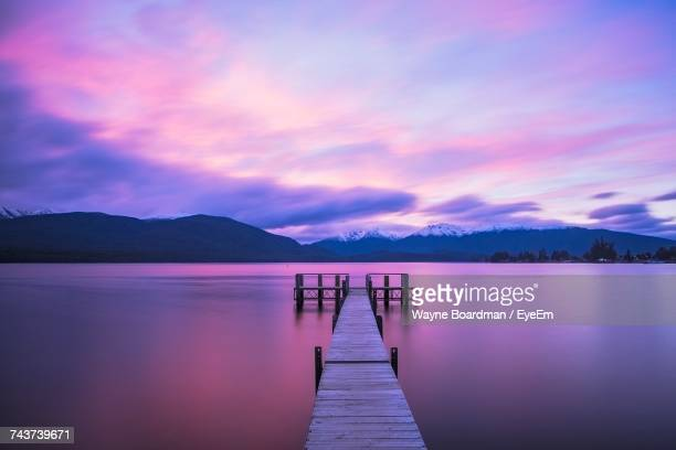 pier over lake against sky during sunset - lilac stock photos and pictures
