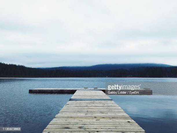 pier over lake against sky - gabby allen stockfoto's en -beelden